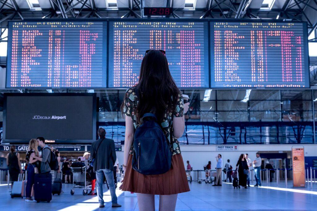 ragazza che guarda l'orario dei voli.